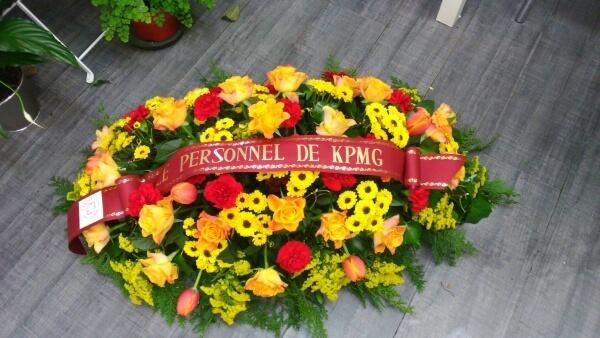 Gerbe de deuil ovale réalisé avec des roses, germini, chrysanthèmes Solidago et oeillets